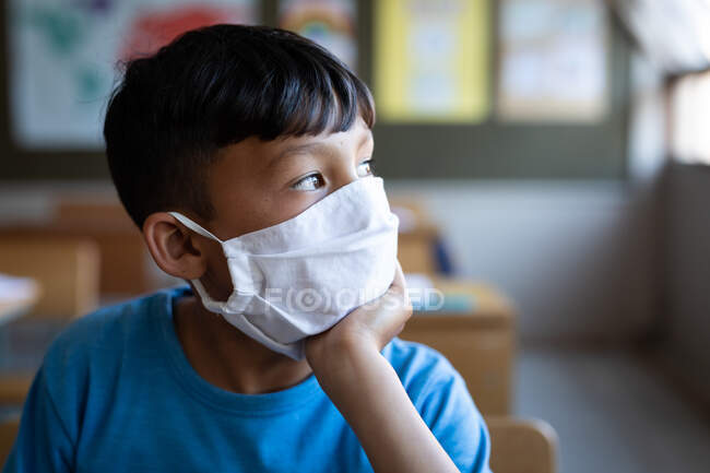 Thoughtful mixed race boy wearing face mask sitting on his desk at school. Primary education social distancing health safety during Covid19 Coronavirus pandemic. — Stock Photo