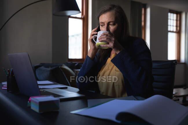 Mulher branca desfrutando de tempo em casa, distanciamento social e auto-isolamento em quarentena, sentada à mesa, usando um laptop, falando em smartphone e bebendo chá. — Fotografia de Stock