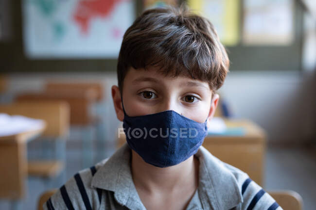 Portrait of a Caucasian boy wearing a face mask, sitting on his desk in class at school. Primary education social distancing health safety during Covid19 Coronavirus pandemic. — Stock Photo