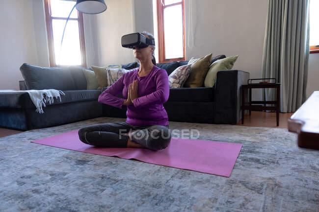 Кавказка наслаждается временем дома, социальным дистанцированием и самоизоляцией в карантинной изоляции, упражнениями в гостиной, в наушниках, сидя на полу, скрестив ноги, медитируя. — стоковое фото