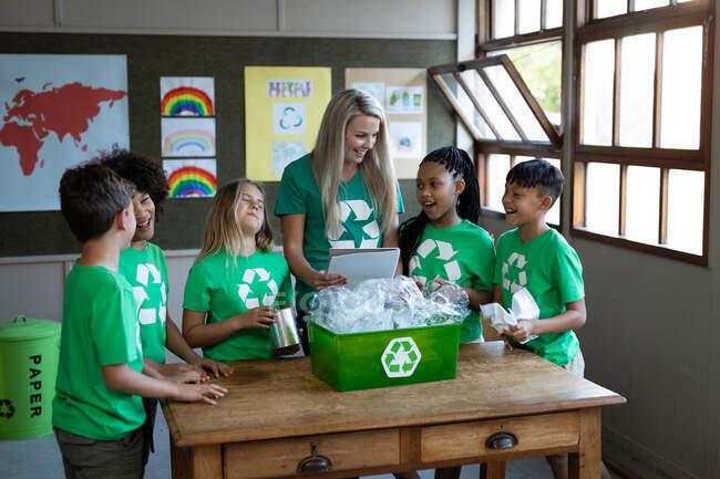 Maestra caucásica y grupo de niños multiétnicos con contenedor de reciclaje en la escuela. Educación primaria distanciamiento social seguridad sanitaria durante la pandemia del Coronavirus Covid19. - foto de stock
