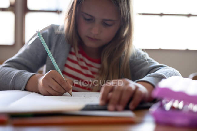 Une fille caucasienne écrit dans un livre alors qu'elle est assise sur son bureau à l'école. Enseignement primaire distanciation sociale sécurité sanitaire pendant la pandémie de coronavirus Covid19. — Photo de stock