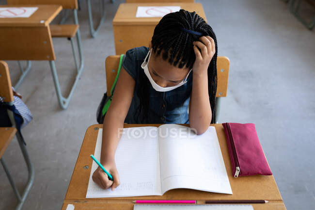 Overhead view of a mixed race girl wearing face mask writing while sitting on her desk in the classroom. Primary education social distancing health safety during Covid19 Coronavirus pandemic. — Stock Photo