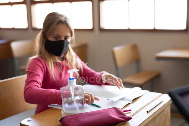 Menina caucasiana usando máscara facial enquanto sentada na mesa e higienizando as mãos. Educação primária distanciamento social segurança sanitária durante Covid19 pandemia de coronavírus. — Fotografia de Stock