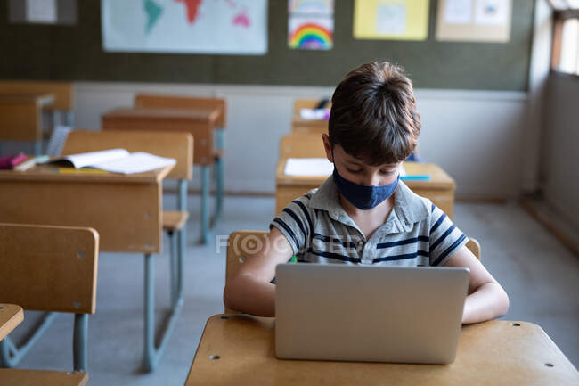Caucasian boy wearing a face mask, using laptop while sitting on his desk in class at school. Primary education social distancing health safety during Covid19 Coronavirus pandemic. — Stock Photo