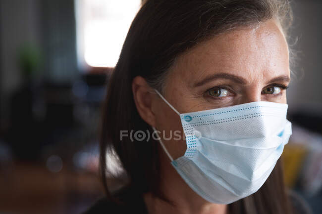 Portrait of Caucasian woman enjoying time at home, social distancing and self isolation in quarantine lockdown, wearing face mask protecting from Covid 19 coronavirus infection, looking at camera. — Stock Photo