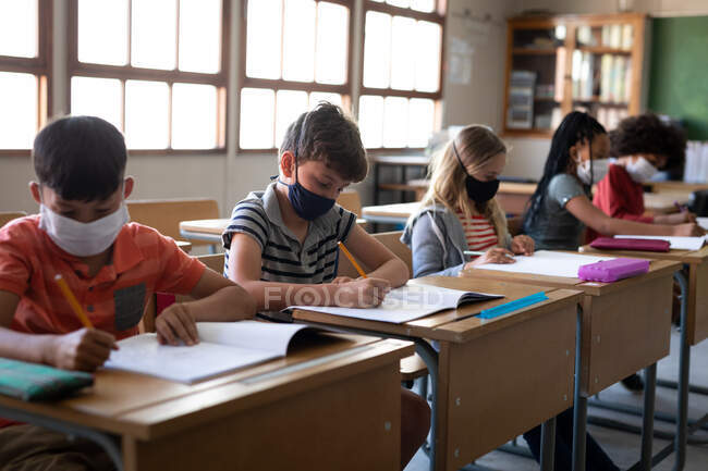Многонациональная группа детей начальной школы, сидящих за партами в масках для лица в классе. Начальное образование Социальное дистанцирование безопасности здоровья во время пандемии Coronavirus Covid19. — стоковое фото