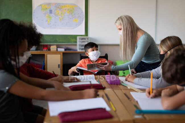 Caucasian female teacher wearing face mask with digital tablet teaching group of multi ethnic kids. Primary education social distancing health safety during Covid19 Coronavirus pandemic. — Stock Photo