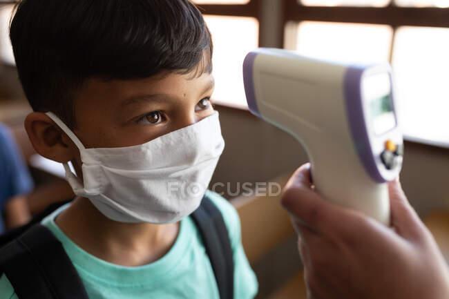 Змішаний хлопчина, одягнений в маску обличчя, отримує температуру в початковій школі. Первинна освіта Соціальна безпека для здоров'я під час пандемії Ковіда19 Коронавірус. — стокове фото