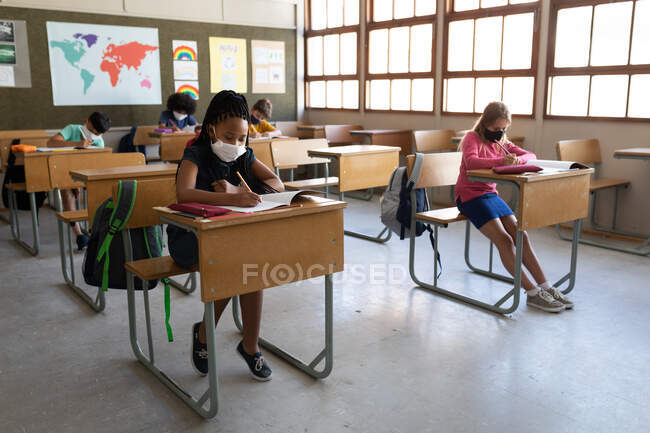 Multi ethnic group of elementary school children sitting at desks wearing face masks in classroom. Primary education social distancing health safety during Covid19 Coronavirus pandemic. — Stock Photo
