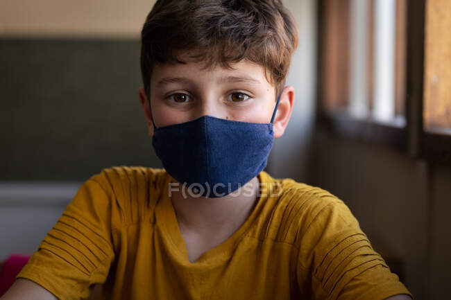 Portrait of a Caucasian boy sitting at desk wearing face mask in classroom. Primary education social distancing health safety during Covid19 Coronavirus pandemic. — Stock Photo