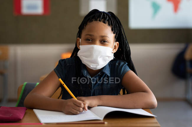 Portrait of a mixed race girl sitting at desk wearing face mask in classroom. Primary education social distancing health safety during Covid19 Coronavirus pandemic. — Stock Photo