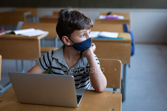 Thoughtful Caucasian boy wearing a face mask, using laptop while sitting on his desk in class at school. Primary education social distancing health safety during Covid19 Coronavirus pandemic. — Stock Photo