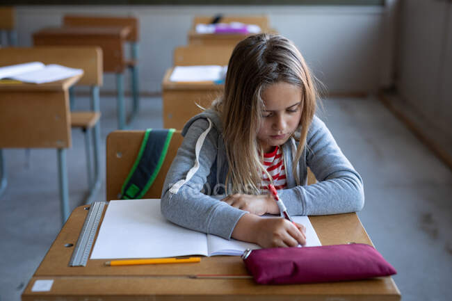 Caucasian girl writing in a book while sitting on her desk at school. Primary education social distancing health safety during Covid19 Coronavirus pandemic. — Stock Photo
