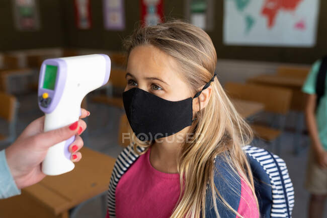 Caucasian girl wearing face mask getting her temperature measured in an elementary school. Primary education social distancing health safety during Covid19 Coronavirus pandemic. — Stock Photo