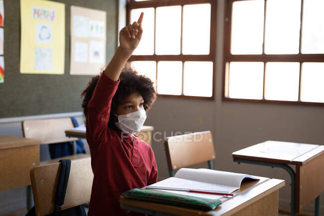 Mixed race boy wearing face mask, sitting on his desk during the lesson. Primary education social distancing health safety during Covid19 Coronavirus pandemic. — Stock Photo
