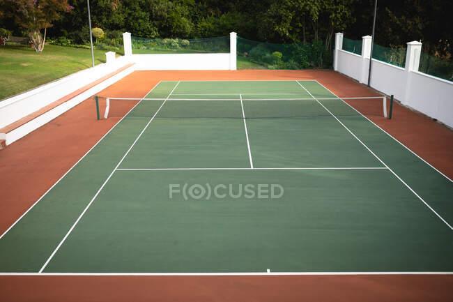 Uma vista de um campo de ténis vazio com uma rede no meio de um dia ensolarado, floresta ao fundo — Fotografia de Stock