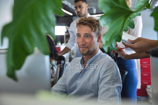 Умный, небрежно одетый кавказский бизнесмен, креативный сидя за столом, улыбаясь, собрался вокруг него, делая заметки. Креативные профессионалы бизнеса, работающие в современном офисе. — стоковое фото