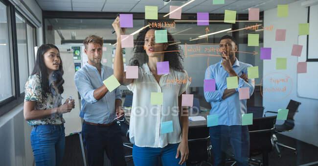Multi-ethnische Männer und Frauen im Business-Team beim gemeinsamen Brainstorming, eine Frau mit gemischter Rasse schreibt auf klebrige Zettel, die an einer Glaswand kleben. Kreative Geschäftsprofis, die in einem modernen Büro arbeiten. — Stockfoto