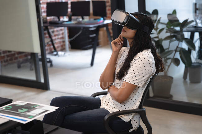 Mixed race woman working in a casual office, wearing vr headset, looking at virtual screen. Social distancing in the workplace during Coronavirus Covid 19 pandemic. — Stock Photo