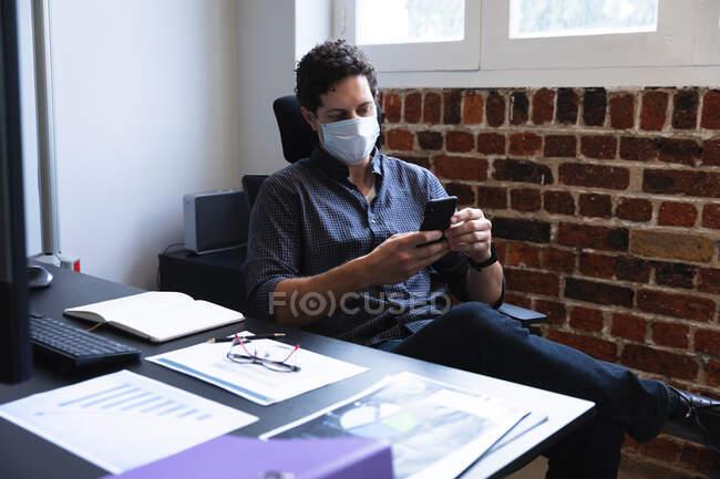 Homme caucasien travaillant dans un bureau décontracté, utilisant son smartphone et portant un masque facial. Distance sociale sur le lieu de travail pendant la pandémie de coronavirus Covid 19. — Photo de stock