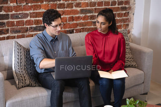 Mixed race woman and Caucasian man working in a casual office, sitting on a sofa, using a laptop computer and talking. Creative business professionals working in a busy modern office. — Stock Photo
