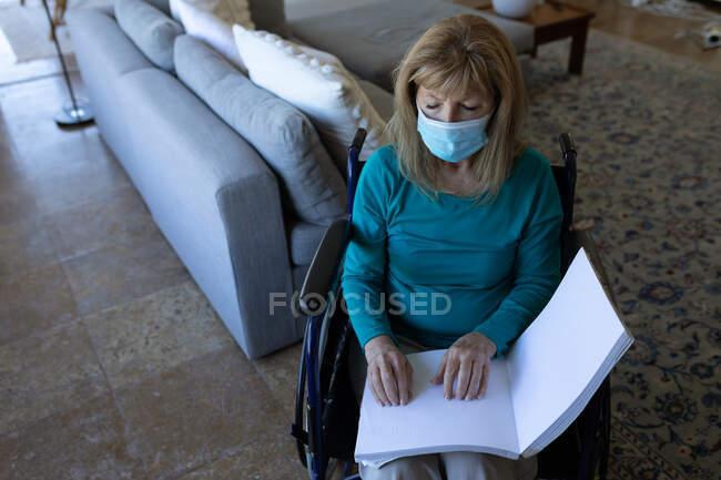 Mujer mayor caucásica pasando tiempo en casa, sentada en silla de ruedas y leyendo un libro con las manos, usando mascarilla. Distanciamiento social durante el bloqueo de cuarentena del Coronavirus Covid 19. - foto de stock