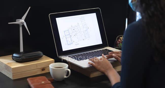 Donna di razza mista che lavora in un ufficio informale, indossa una maschera facciale, usando un computer portatile. Distanze sociali sul luogo di lavoro durante la pandemia di Coronavirus Covid 19. — Foto stock