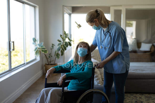 Senior Caucasian woman at home visited by Caucasian female nurse, sitting on wheelchair, wearing face masks. Medical car — Stock Photo
