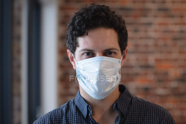 Portrait of Caucasian man working in a casual office, wearing face mask and looking at camera. Social distancing in the workplace during Coronavirus Covid 19 pandemic. — Stock Photo