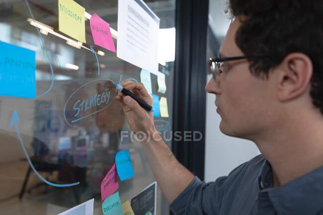 Homem caucasiano trabalhando em um escritório casual, escrevendo em uma placa de vidro. Distanciamento social no local de trabalho durante a pandemia do Coronavirus Covid 19. — Fotografia de Stock