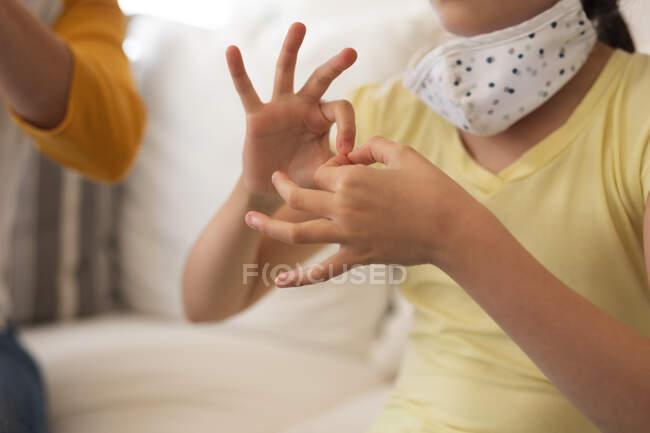 Mujer y su hija pasando tiempo en casa juntas, usando máscaras faciales, teniendo una conversación usando lenguaje de señas. Distanciamiento social durante el bloqueo de cuarentena del Coronavirus Covid 19. - foto de stock
