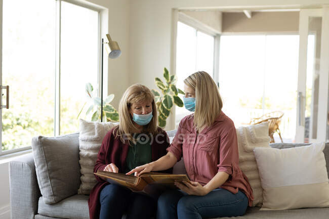 Senior Caucasian woman spending time at home with her adult daughter, sitting on couch, wearing face masks and reading a book. Social distancing during Covid 19 Coronavirus quarantine. — Stock Photo