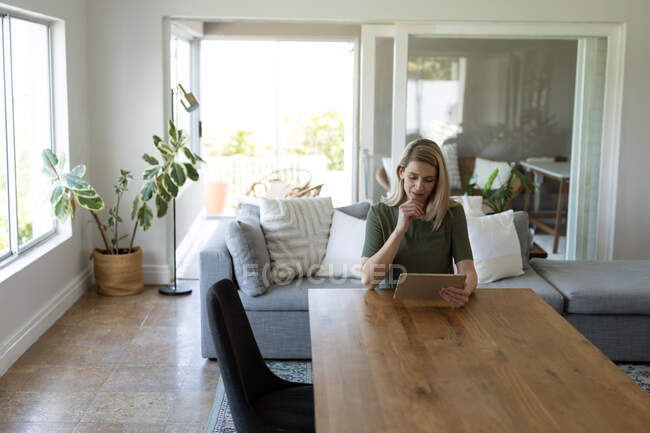 Caucasian woman spending time at home, sitting at a table, using digital tablet. Social distancing during Covid 19 Coronavirus quarantine. — Stock Photo