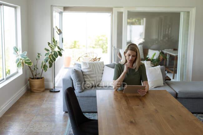 Kaukasische Frau verbringt Zeit zu Hause, sitzt an einem Tisch und benutzt ein digitales Tablet. Soziale Distanzierung während Covid 19 Coronavirus Quarantäne. — Stockfoto