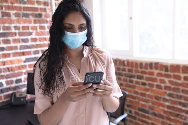 Femme de race mixte travaillant dans un bureau décontracté, utilisant son smartphone et portant un masque facial. Distance sociale sur le lieu de travail pendant la pandémie de coronavirus Covid 19. — Photo de stock