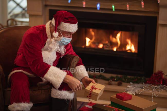 Uomo anziano caucasico a casa vestito da Babbo Natale, con la maschera facciale, seduto su una sedia accanto al camino, a fare regali. Distanza sociale durante il blocco di quarantena Covid 19 Coronavirus. — Foto stock