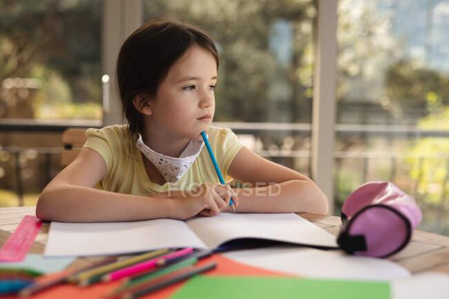 Chica caucásica pasando tiempo en casa, usando mascarilla, haciendo tareas escolares. Distanciamiento social durante el bloqueo de cuarentena del Coronavirus Covid 19. - foto de stock