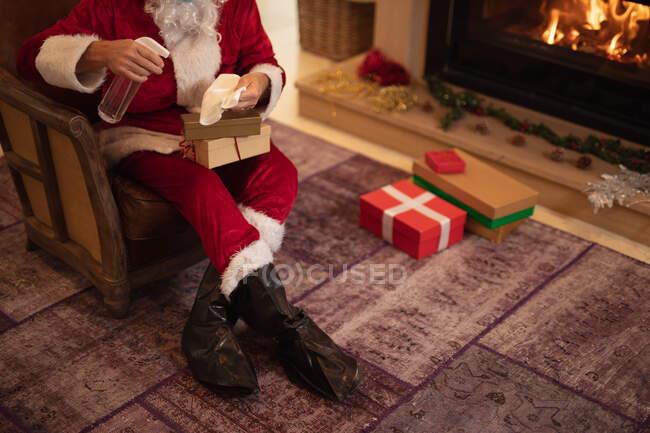 Uomo anziano caucasico a casa vestito da Babbo Natale, che disinfetta un regalo. Distanza sociale durante il blocco di quarantena Covid 19 Coronavirus. — Foto stock