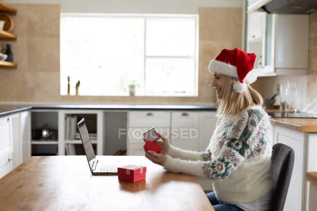 Kaukasische Frau verbringt Zeit zu Hause, sitzt zu Weihnachten mit Weihnachtsmütze in der Küche und benutzt Laptop mit Geschenken auf dem Tisch. Soziale Distanzierung während Covid 19 Coronavirus Quarantäne. — Stockfoto