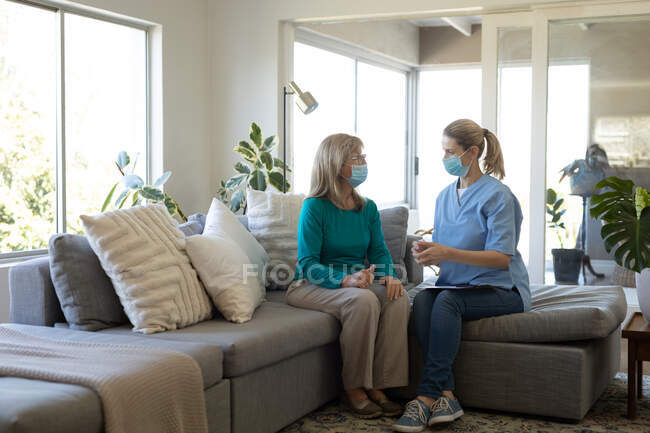 Senior Caucasian woman at home visited by Caucasian female nurse, sitting on couch, talking and wearing face masks. Medical care at home during Covid 19 Coronavirus quarantine. — Stock Photo