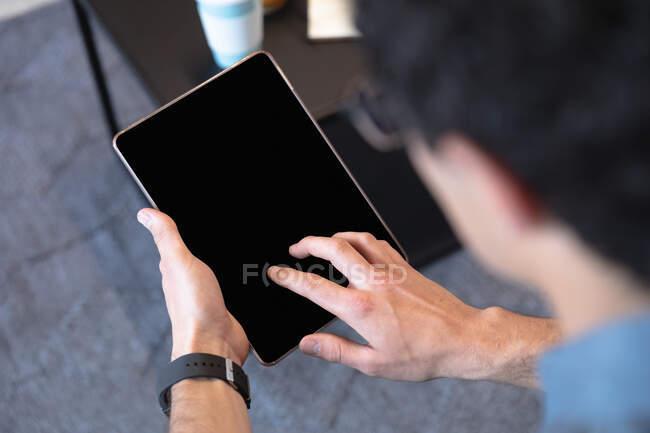 Uomo caucasico che lavora in un ufficio informale, seduto su un divano, usando un tablet. Distanze sociali sul luogo di lavoro durante la pandemia di Coronavirus Covid 19. — Foto stock