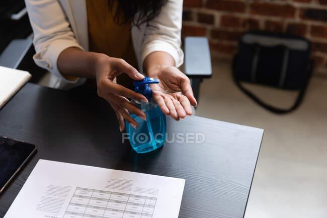 Primo piano di una donna che lavora in un ufficio informale, usando disinfettante. Distanze sociali sul luogo di lavoro durante la pandemia di Coronavirus Covid 19. — Foto stock