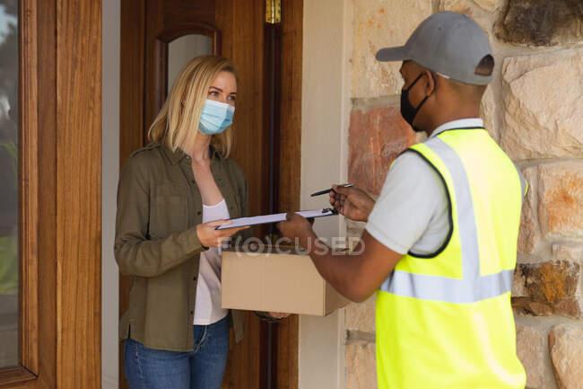 Kaukasische Frau, die Zeit zu Hause verbringt, Gesichtsmaske trägt und ein Paket vom Zusteller erhält. Soziale Distanzierung während Covid 19 Coronavirus Quarantäne Lockdown. — Stockfoto