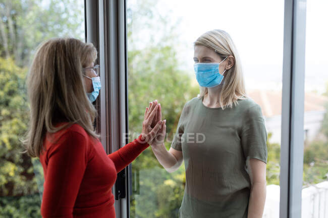 Senior Caucasian woman and her adult daughter at home, wearing face masks and greeting each other by touching hands. Social distancing, health and hygiene during Covid 19 Coronavirus pandemic. — Stock Photo