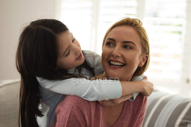 Caucasian woman and her daughter spending time at home together, sitting on a sofa, embracing. Social distancing during Covid 19 Coronavirus quarantine lockdown. — Stock Photo