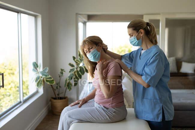 Mulher branca sênior em casa visitada por enfermeira caucasiana, esticando o pescoço, usando máscaras faciais. Cuidados médicos em casa durante a quarentena do Coronavirus Covid 19. — Fotografia de Stock