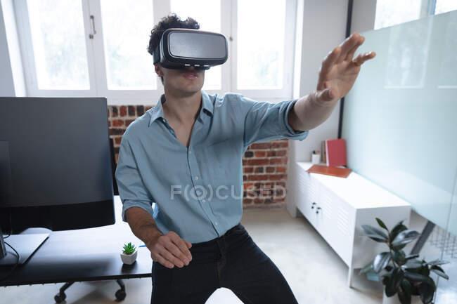 Hombre caucásico trabajando en una oficina informal, usando auriculares vr, tocando la pantalla virtual. Distanciamiento social en el lugar de trabajo durante la pandemia de Coronavirus Covid 19. - foto de stock