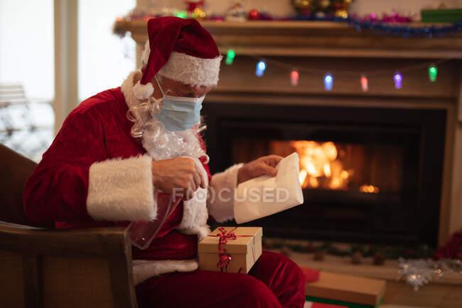 Uomo anziano caucasico a casa vestito da Babbo Natale, con la maschera facciale, che disinfetta un regalo. Distanza sociale durante il blocco di quarantena Covid 19 Coronavirus. — Foto stock