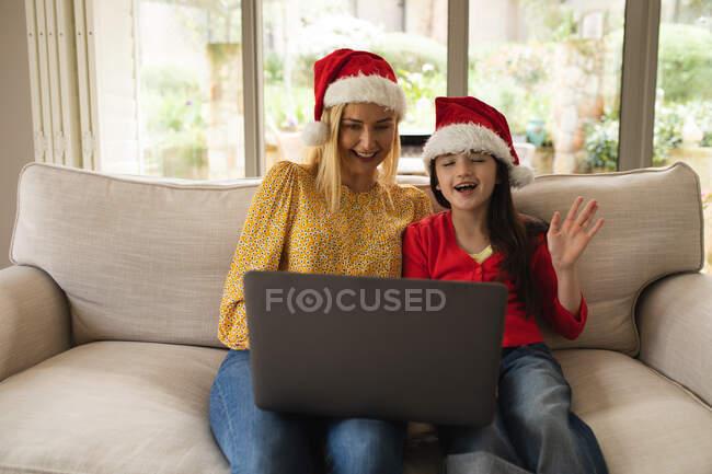 Donna caucasica e sua figlia passano del tempo a casa insieme, indossando cappelli da Babbo Natale, usando un computer portatile, facendo una videochiamata. Distanza sociale durante il blocco di quarantena Covid 19 Coronavirus. — Foto stock
